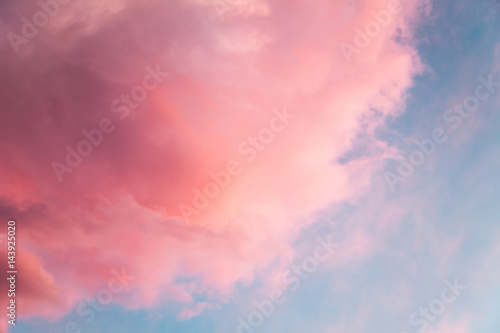 Beautiful sky background with pink fluffy colored cloud looks like cotton candy or candy-floss at sunset with sun setting down.