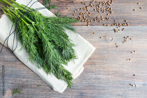 Fotomural Bunch of fresh dill herbs and coriander seeds on wooden table, top view, copy space