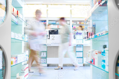 Photo sur Toile Pharmacie Defocused picture of customers shopping in pharmacy .