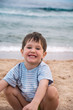 Portrait of a happy little boy against the sea