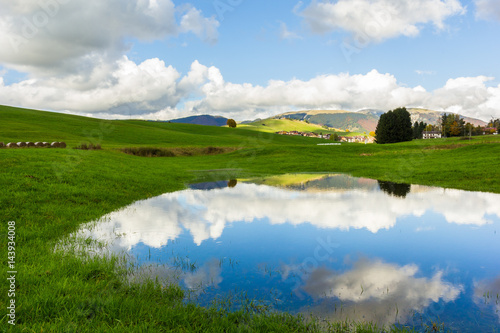Fotobehang Cultuur Lake, Altopiano of Asiago, Province of Vicenza, Veneto, Italy. Small spring lake in field.