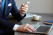 Side view closeup of unrecognizable modern businessman holding smartphone and browsing internet while working with laptop in cafe