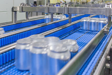 Aluminum Beverage Cans For Drinks Move On Conveyor Belt At Large Factory. Shallow Depth Of Field.
