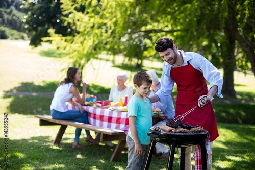 Photo Father and son barbequing in the park