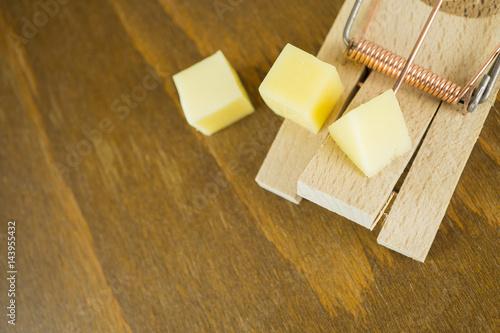 Photo  Drei Käsewürfel auf einer Mausefalle, Holzhintergrund und Textfreiraum