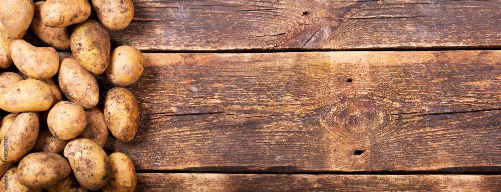 Fotografia fresh potatoes on wooden table
