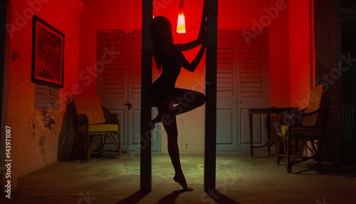 obraz lub plakat Sexy Woman Silhouette Dancing at the Hotel. Pole Dancer female Stripper in the Night Sensual Red light, noir style
