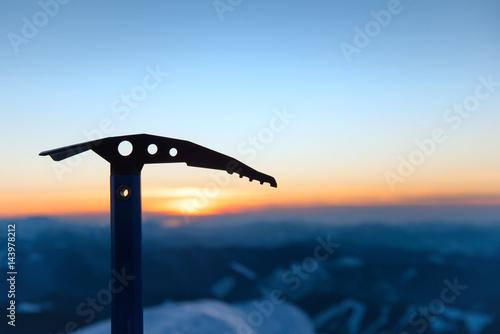Poster de jardin Alpinisme Silhouette of iceaxe against sunset