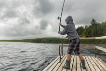 Teen Boy Fishing On Wooden Pier