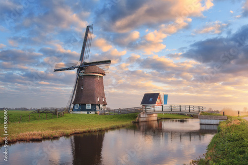 Poster Molens Windmill near the water canal at sunrise in Netherlands. Beautiful old dutch windmill and colorful sky with clouds. Rustic landscape in Holland. Sunny morning. Sky reflected in water. Amazing scene