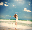 photo of beautiful young woman jumping on the sunny coast on the sky and sea backgrond