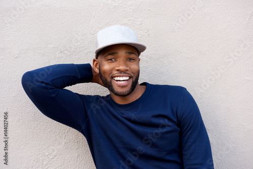 Fotografia  attractive man standing with hand behind head and smiling by wall