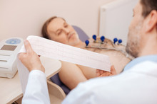 Excellent Trained Cardiologist Carefully Studying Patients Cardiogram
