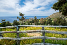 Old Wooden Fence With A Field Of Flowers And The Sea At The Background, Crete, Greece.