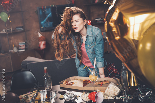 Obraz na plátně Depressed young woman with hangover leaning at messy table after party