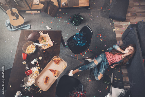 Fotografering  Top view of young drunk woman lying on floor in messy room