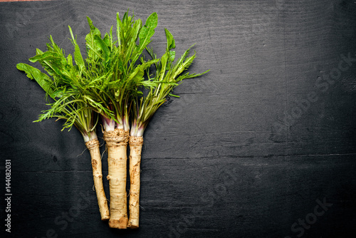 Fresh horseradish. On the black Wooden desk. Top view. Canvas-taulu