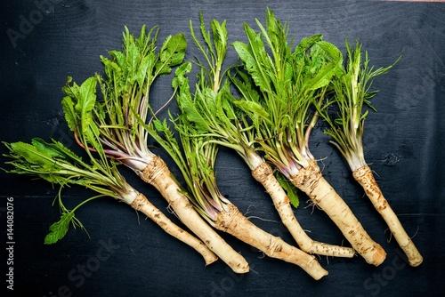 Fotografie, Obraz  Fresh horseradish. On the black Wooden desk. Top view.
