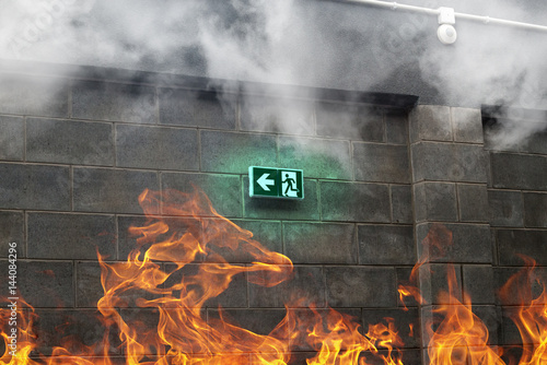 Fotografia Emergency Fire Exit on the stone wall with fire and smoke