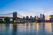 Brooklyn Bridge and Manhattan skyline at dusk, viewed from the East River, New York City