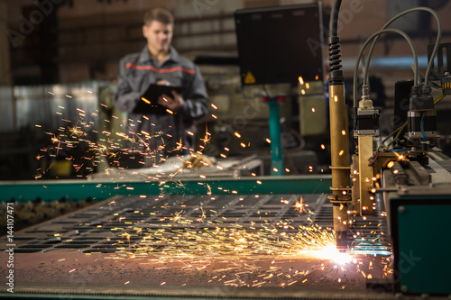 Fotografía  Industrial worker operating plasma cutter at the metal factory