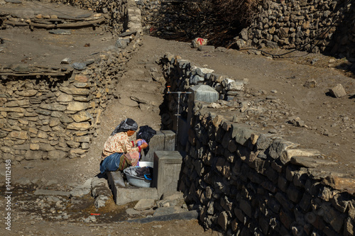 Wall Murals Nepal Nepalese woman is washing clothes