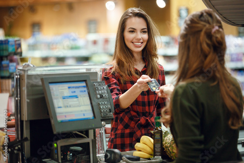 Smiling young lady standing in supermarket holding credit card