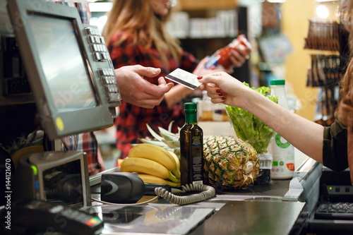 Fototapeta Cropped picture of young man gives credit card to cashier obraz