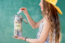 Young Woman Puuting Money Into The Jar With Savings For Summer Vacation Standing On The Green Background
