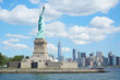 Statue of Liberty island and New York city skyline in a sunny day, blue sky and white clouds