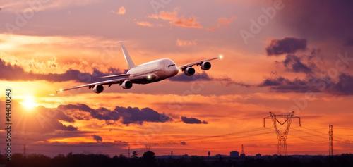 Türaufkleber Flugzeug Commercial airplane flying above city in sunset ligt
