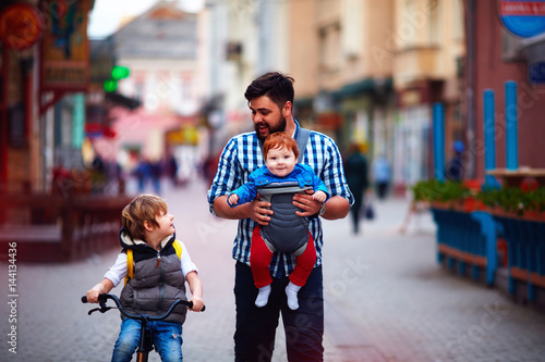 Photo  happy father and two sons on the city walk