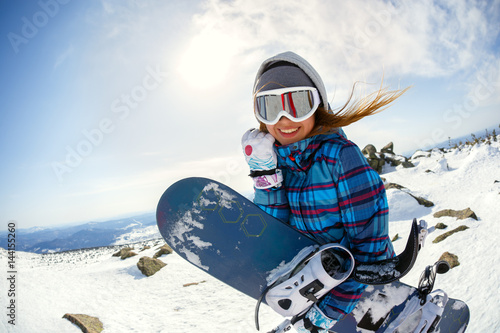 Fotobehang Wintersporten Girl snowboarder enjoys the ski resort