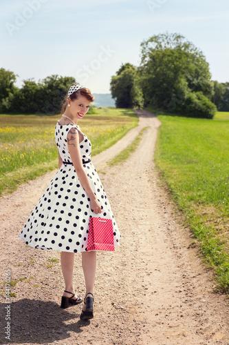 Valokuvatapetti Rockabilly oder Pinup Girl mit kleiner Tasche läuft auf einem Feldweg in der Nat