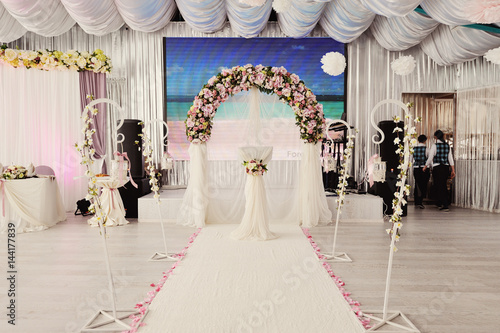 Valokuva  the beautiful wedding hall decorated with a decor in gentle white and powdery to