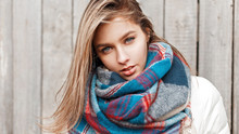 Portrait Of A Young Girl With Blue Eyes With A Bright Colored Scarf On A Gray Background