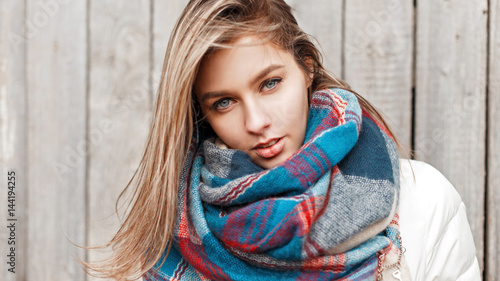 Fotografie, Obraz  Portrait of a young girl with blue eyes with a bright colored scarf on a gray ba