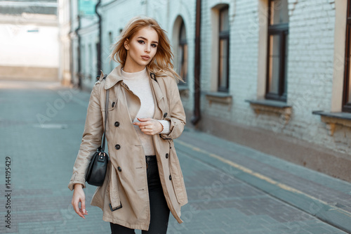 Fotografie, Tablou  Beautiful young woman in a trendy coat with a black bag walks in the city