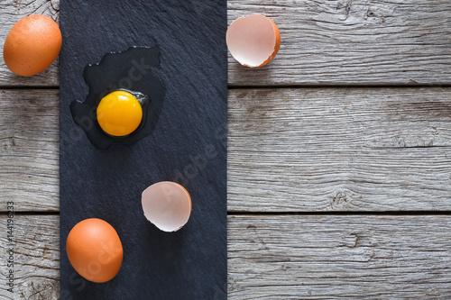 Plakat Brown organicznie pękający jajka z yolk na czarnym drewnianym tle