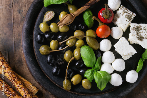 Recess Fitting Appetizer Mediterranean appetizer antipasti board with green black olives, feta cheese, mozzarella, capers, pepper, basil with grissini bread sticks over black wood burnt background. Top view with space
