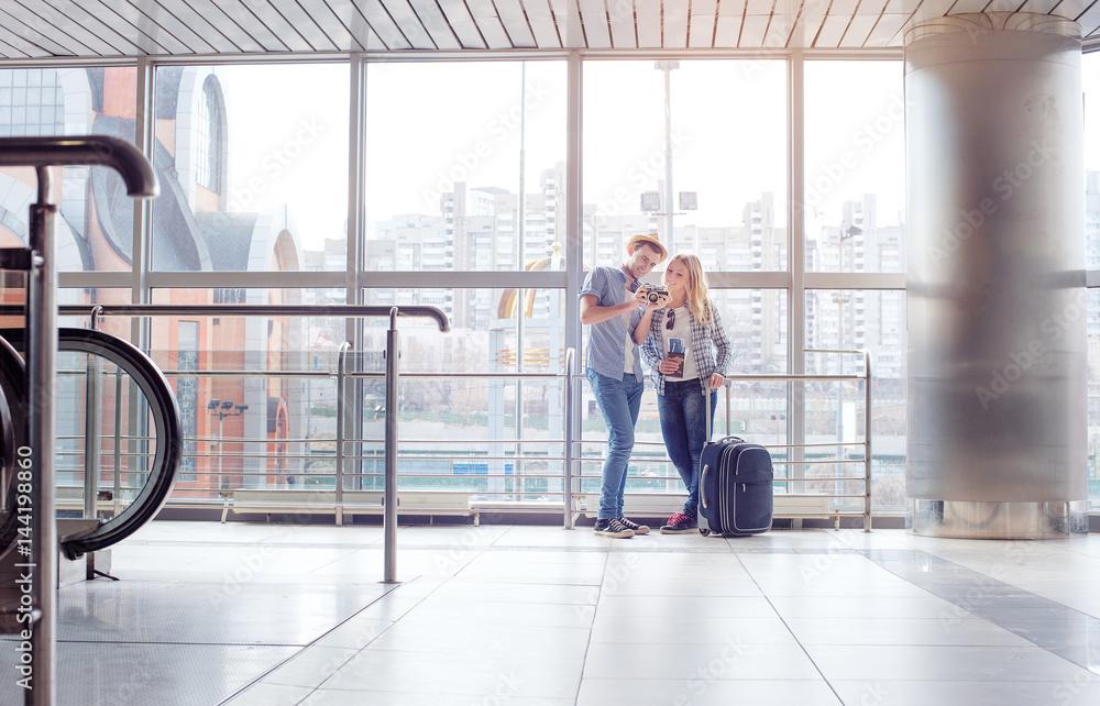 Fototapeta Couple standing in airport terminal holding camera.