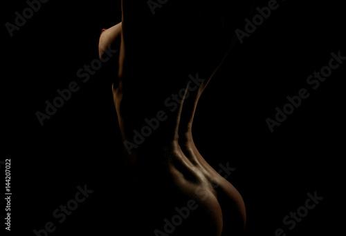 Zdjęcie XXL seksowna kobieta z nagą klatką piersiową i pośladkami na czarnym tle