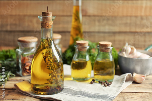 Papiers peints Herbe, epice 2 Olive oil with spices on wooden background