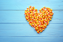 Colorful Halloween Candy Corns In Heart Shape On Wooden Background