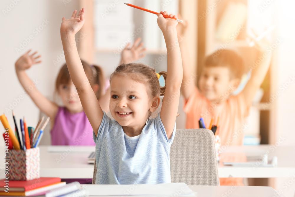Fototapeta Cute girl at lesson in classroom