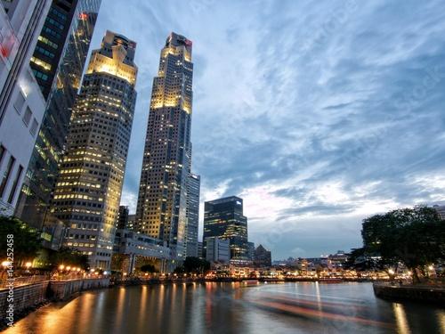 port-w-singapurze-smuga-plynacej-lodzi-i-oswietlone-budynki