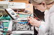woman repairing computer hardware in service center. Repairing and fixing service in lab. Electronics repair service concept.