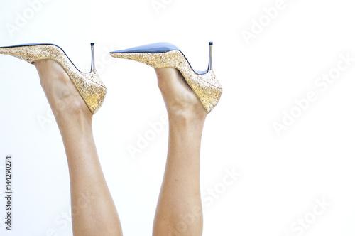Photo  Frauenbeine mit goldenen Stöckelschuhen ragen in die Luft
