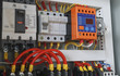 Close-up electrical wiring with fuses and contactors in control panel box of machine.
