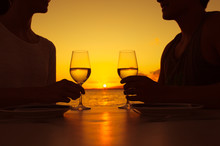 Couple Enjoying A Glass Of Wine Against A Beautiful Sunset.